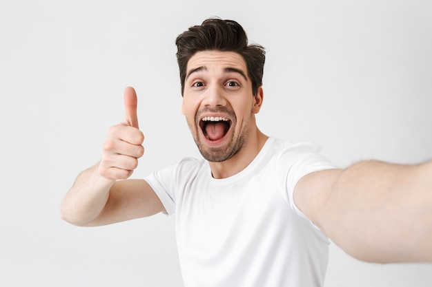Image of excited happy young man posing isolated over white wall  make a selfie by camera showing thumbs up gesture.
