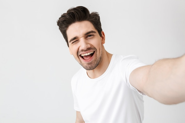 Image of excited happy young man posing isolated over white wall  make a selfie by camera.