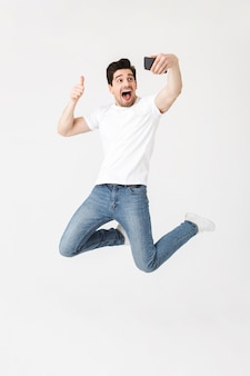 Image of excited happy young man posing isolated over white wall  using mobile phone take a selfie make a thumbs up gesture.