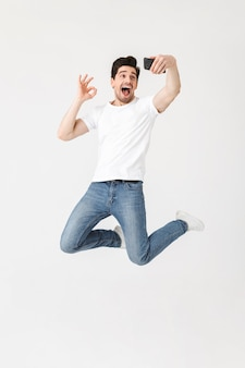 Image of excited happy young man posing isolated over white wall  using mobile phone take a selfie showing okay gesture.