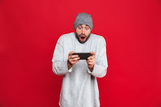 Image of excited man 30s holding smartphone and playing video games, isolated