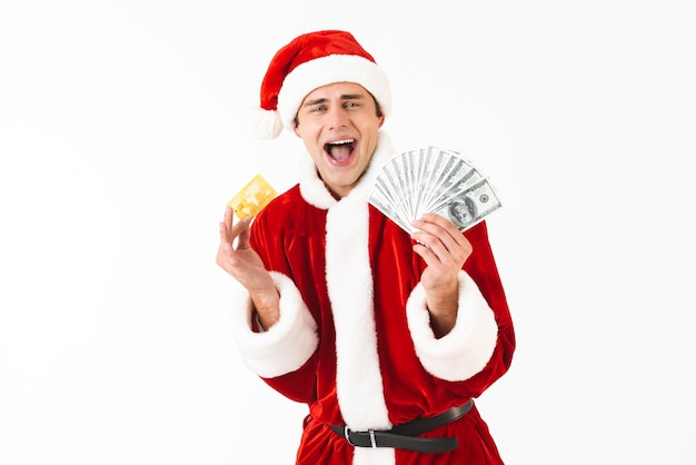 Image of excited man 30s in santa claus costume holding dollar bills and credit card