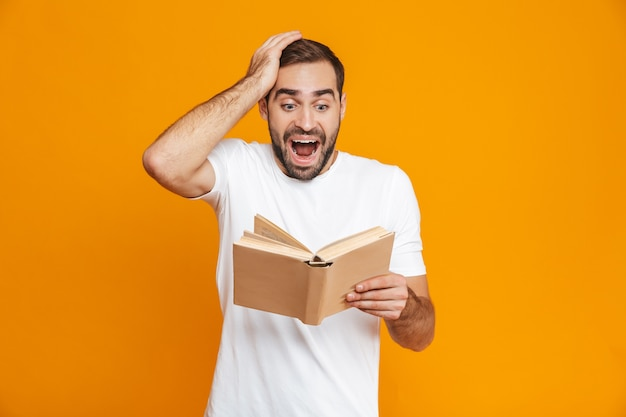 Image of excited man 30s in white t-shirt holding and reading book, isolated
