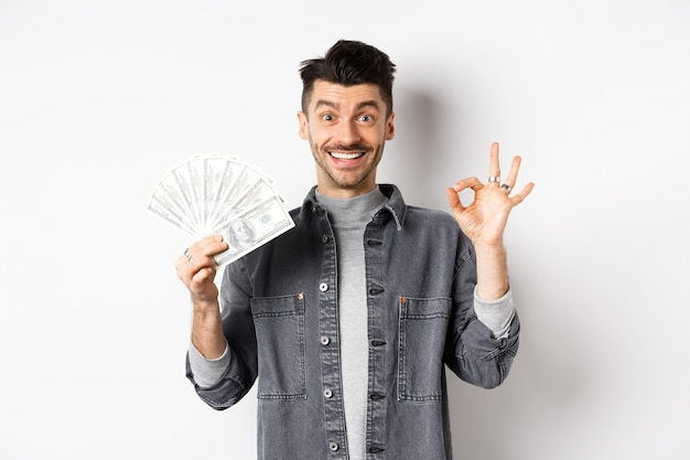 Image of excited man holding dollar bills and show okay sign with happy face, making money, standing on white background.