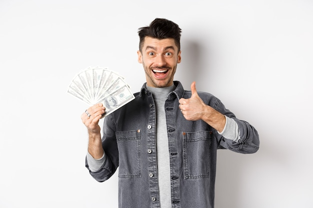 Image of excited man holding dollar bills and show thumbs-up with happy face, making money, standing on white background.