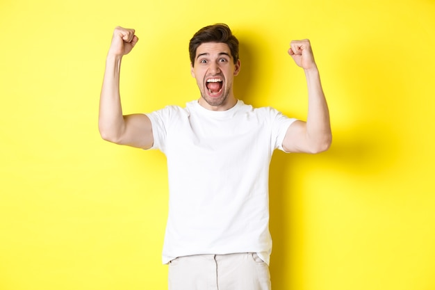 Image of excited man winning, raising hands up and celebrating, triumphing and rooting for team, standing over yellow background. copy space