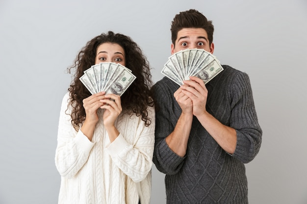 Image of excited man and woman holding fan of dollar money, isolated over gray wall