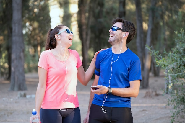 Image of excited man and woman with headphones listening to music on cell phones in the park