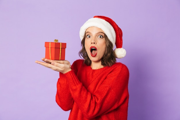 Image of an excited shocked young woman wearing christmas hat isolated over purple wall holding surprise gift box.