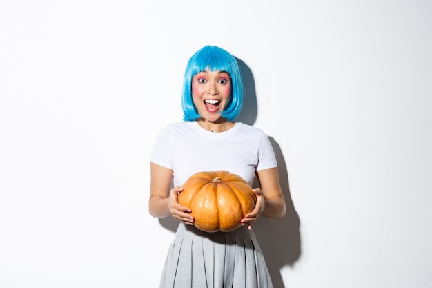 Image of excited smiling asian woman celebrating halloween, holding big pumpkin, wearing blue wig for party, standing.