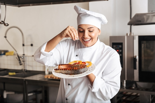 Image of excited woman chef wearing white uniform, holding plate with grilled fish in kitchen at the restaurant