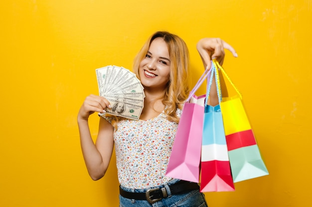 Image of a excited  young blonde girl holding banknotes and shopping bag  over yellow wall