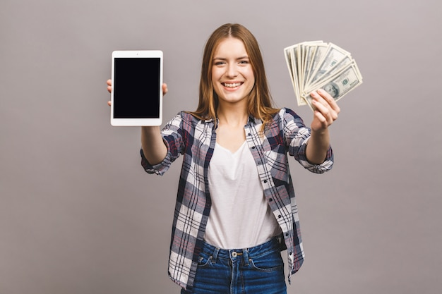 Image of excited young lady. looking camera showing display of tablet computer holding money.