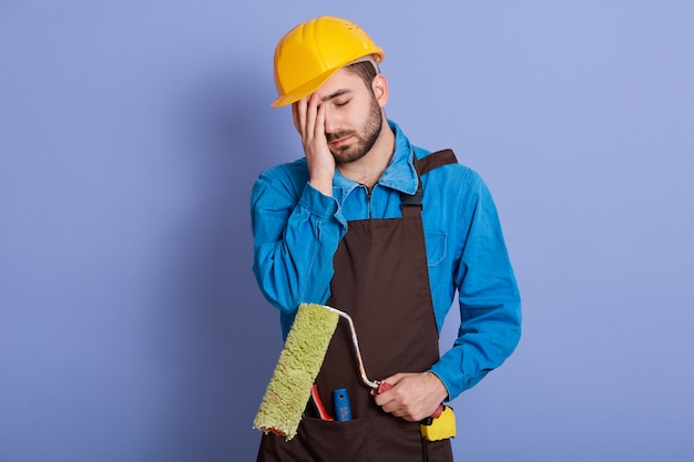 Image of exhausted professional builder wearing brown apron