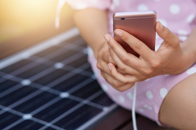 Image of faceless woman in pink dress charging her smart phone on free multipurpose solar panel charger, free energy for everyone