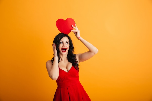 Image of fascinating woman 20s in red dress smiling and holding paper valentine heart above head, isolated over yellow wall