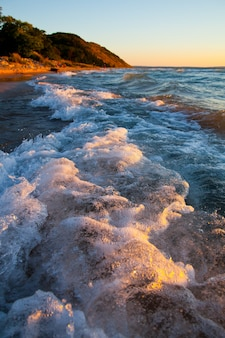 Image of foamy white crest of waves crash against the beach with a mountain in the background