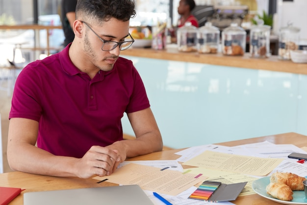 Image of focused male student prepares report in finances, looks attentively at papers, eats delicious croissants, poses over cafe interior with free space for your promotion. freelance work
