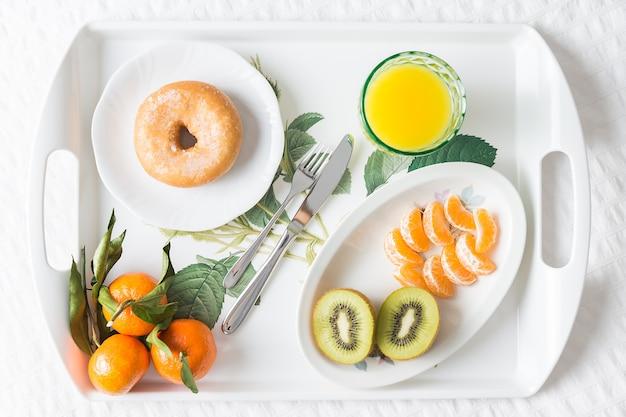 Изображение сверху подноса с пончиком на завтрак с мандарином, киви и апельсиновым соком на белой кровати с естественным освещением