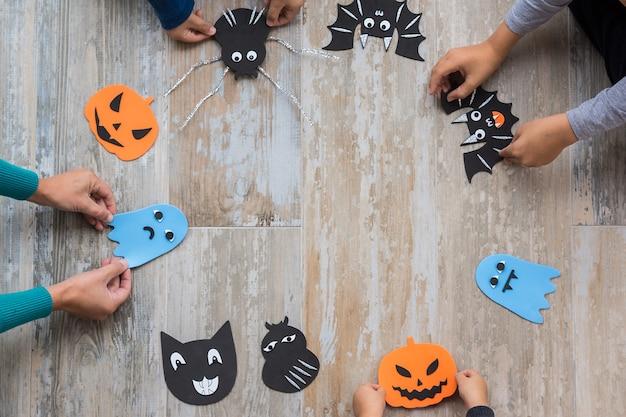 Изображение сверху с мотивами хэллоуина для украшения помещено в круг на старом деревянном полу, дети и мама держат их за руки