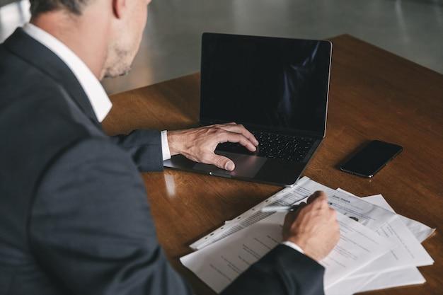 흰색 셔츠와 검은 양복을 입고 사무실에서 테이블에 앉아 노트북을 보는 사무적인 남자 뒤에서 이미지, 문서 작업 중