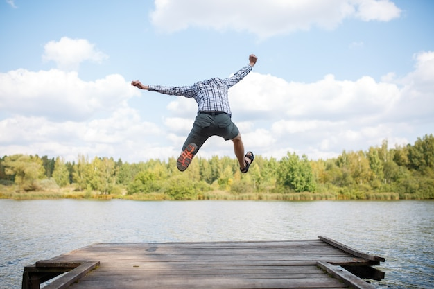 Изображение со спины прыгающего человека на деревянном мосту у реки