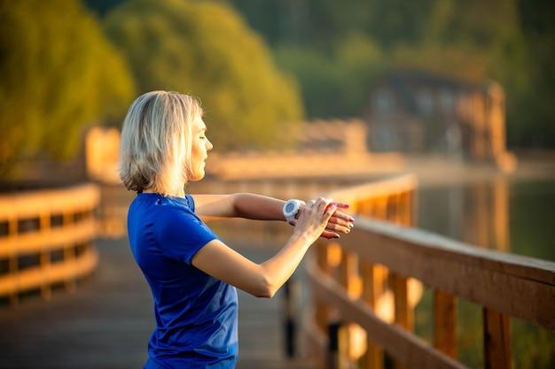 뒤에서 본 스포티한 여성은 여름날 공원의 나무 다리에 서서 시계를 보고 있다