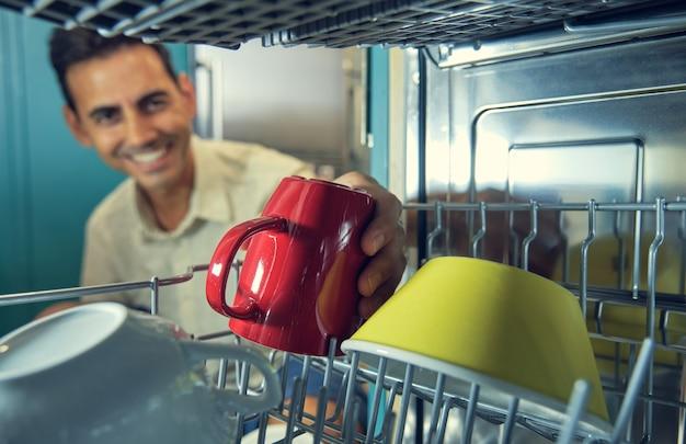 전경에 있는 노란색 그릇 옆에 있는 빨간 머그를 집어들면서 초점을 잃고 웃고 있는 한 청년의 식기세척기 내부 이미지