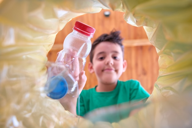 Изображение из мусорной корзины с желтым пакетом, на котором ребенок бросает пластиковую бутылку на переработку, лицо ребенка не в фокусе