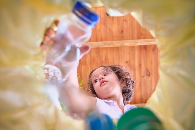 Изображение из мусорного ведра с желтым пакетом, на котором девушка бросает пластиковую бутылку на переработку; бутылки не в фокусе