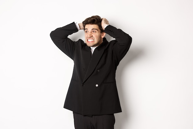 Image of frustrated and angry businessman in black suit, ripping hair on head and grimacing mad, looking left at disaster, standing tensed against white background.