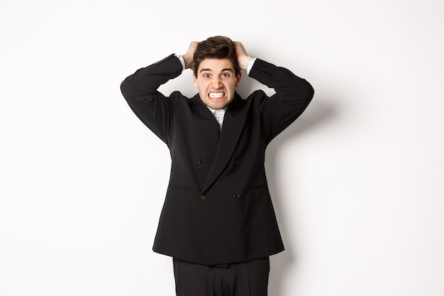 Image of frustrated and angry businessman in black suit, ripping hair on head and grimacing mad, standing tensed against white background.
