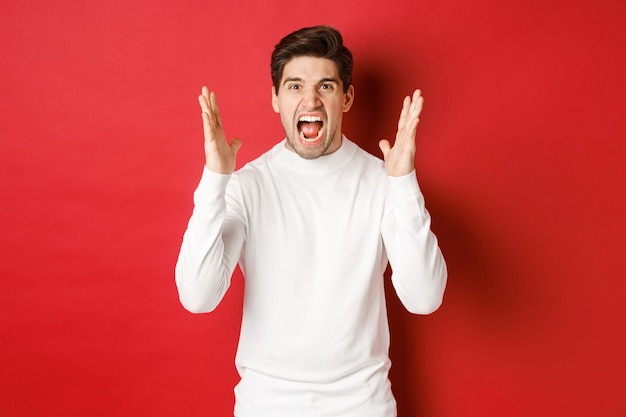 Immagine di un uomo frustrato e arrabbiato con un maglione bianco che grida di rabbia essere arrabbiato con qualcuno in piedi...