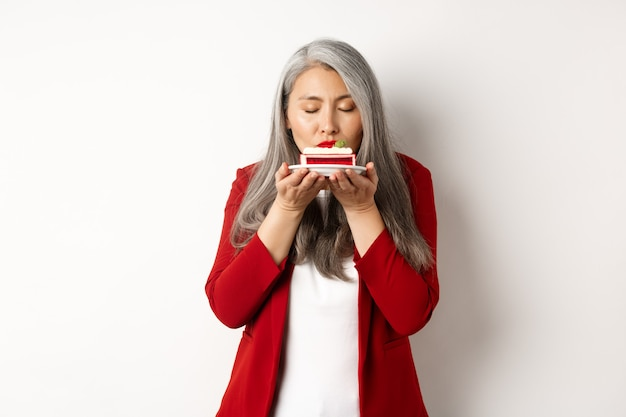 Image of funny asian senior lady sniffing delicious cake, smell dessert with satisfied face, standing over white background.
