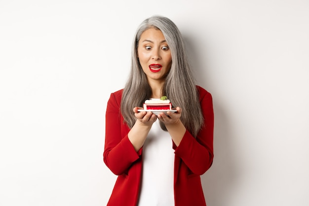 Image of funny asian senior woman looking tempted at piece of cake, desire to bite dessert, standing over white background.