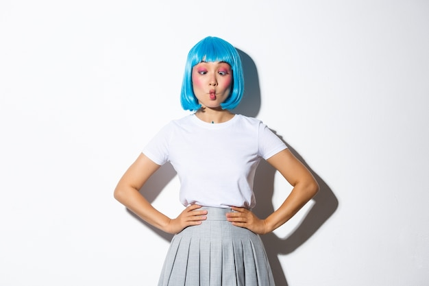 Image of funny cute asian woman in blue wig suking lips to make grimaces, joking around, dressed for halloween party or celebration event, standing.