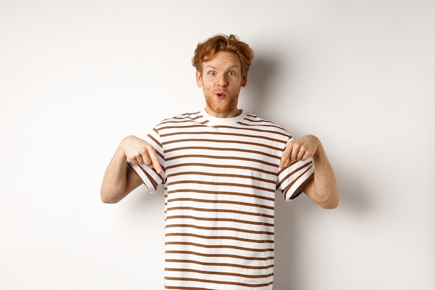 Image of funny redhead male student pointing fingers down, showing promo offer with excited smile, standing over white background.
