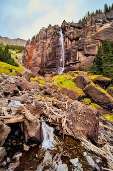 Image of gigantic waterfall over vertical cliffs leading to boulders of moss in valley
