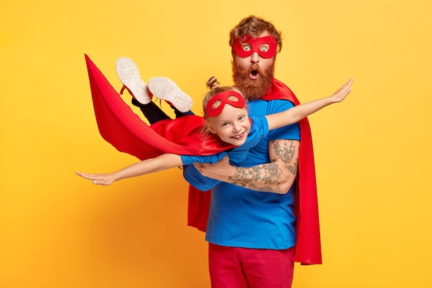 Image of ginger father and daughter dressed in superheroes