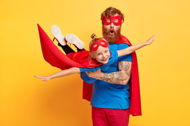 Immagine del padre e della figlia dello zenzero vestiti di supereroi