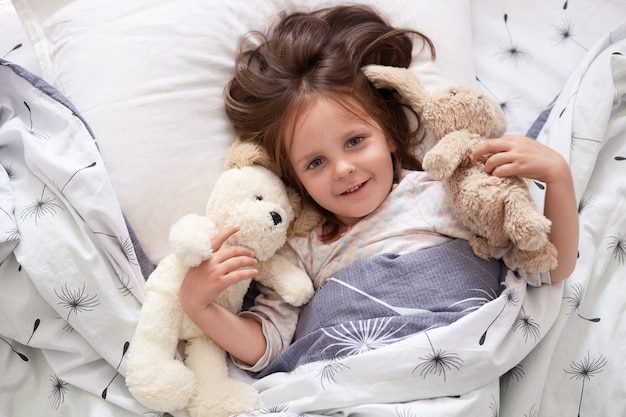 Image of girl lying with fluffy teddy bear and dog before giving them big hug, beautiful kid relaxing in bed with her toy