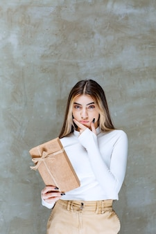Image of a girl model holding a paper present over stone