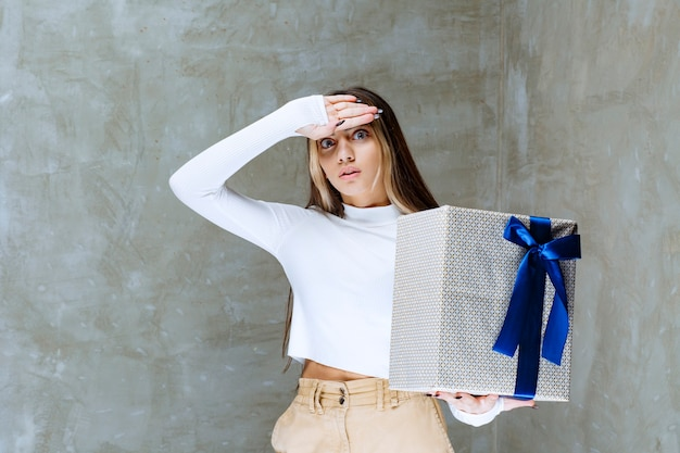 Image of a girl model holding a present box with bow isolated over stone