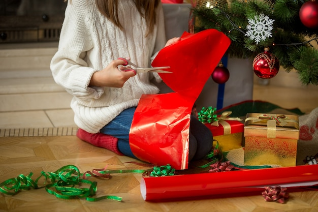 Image of girl sitting under christmas tree and cutting wrapping paper