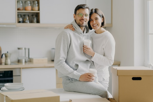 Image of glad family couple hug and stand closely to each other, drink takeout coffee, look with smile at camera, dressed in casual clothes, surrounded with cardboard boxes, spend free time in kitchen