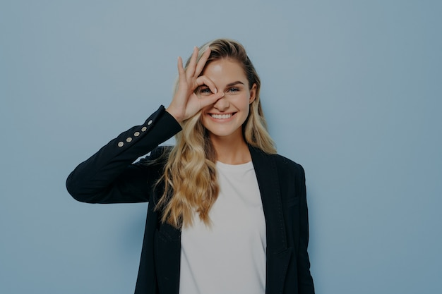Image of glad happy young female with long blonde hair in black blazer and white shirt, making ok gesture with hand and looking through her fingers, rejoicing good day, showing how great she is doing
