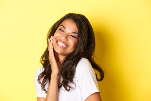 Image of gorgeous african-american woman touching her face, smiling pleased and looking left at copy space, standing over yellow background