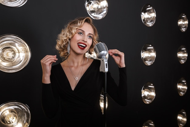 Image of gorgeous artist woman in elegant dress singing into microphone