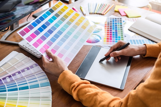 Image of graphic designer working on color selection and drawing on graphics