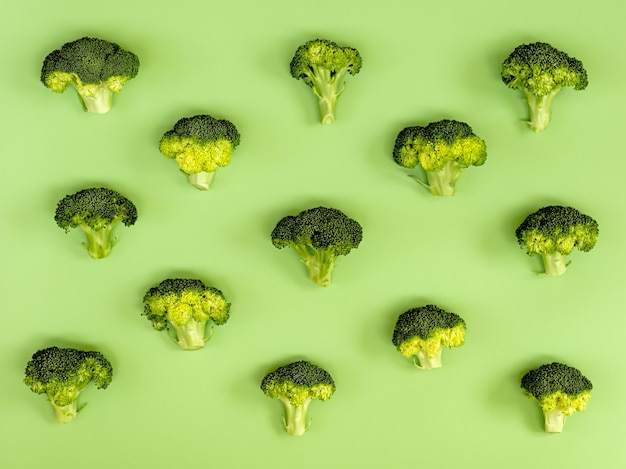 Image of a group of raw broccoli placed on a green cardboard